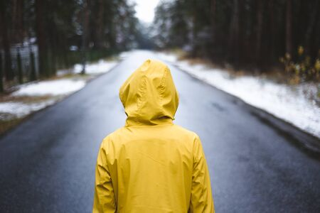 Person in the yellow raincoat is standing on the road in the middle of the forest. Imagens - 131986448