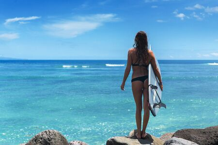 Surfer woman wearing bikini with a blue board against the backdrop of the ocean and blue sky with clouds Imagens - 133386976