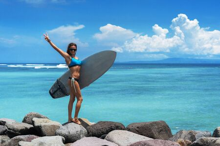 Joyful brunette woman stands on the rocks on the background of the sea and cloudy sky. She wears blue bikini, sunglasses and holds a surfboard. Woman shows a V gesture