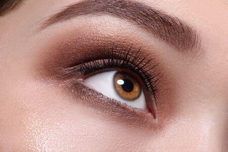 Ojo marrón con maquillaje glamour de cerca