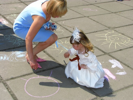 May 9. Victory Day. Woman and girl with the St. George ribbon draw with chalk on asphalt