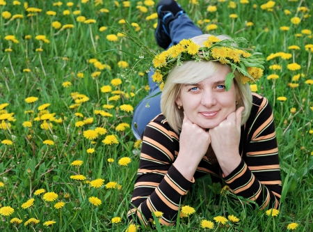 Spring  Green meadow of yellow flowers  The woman lies on the grass with a wreath on head photo