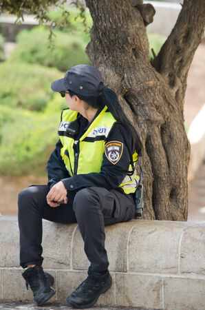 Israeli woman in police uniform sitting on the parapet in city of Jerusalem