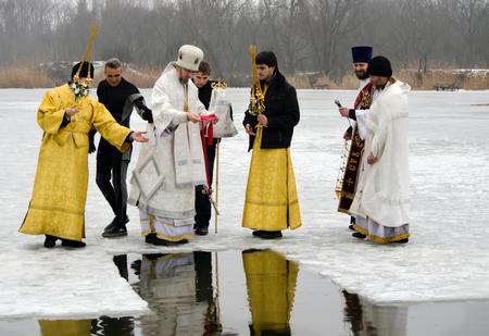 pila bautismal: Obispo Eulogio Novomoskovskiy santifica el agua en un día de fiesta religiosa cristiana de la Epifanía