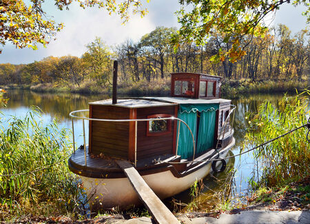 beautiful location: Autumn, water, landscape. Small ship, standing on the quay of the river, in a beautiful location Editorial