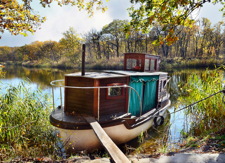 beautiful location: Autumn, water, landscape. Small ship, standing on the quay of the river, in a beautiful location Stock Photo
