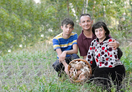 husband wife: Family, husband, wife and son in the forest in a clearing with a basket of mushrooms