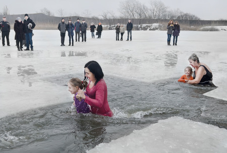 believers: Children, little girls with adults swimming in the river in the winter Christian holiday Epiphany