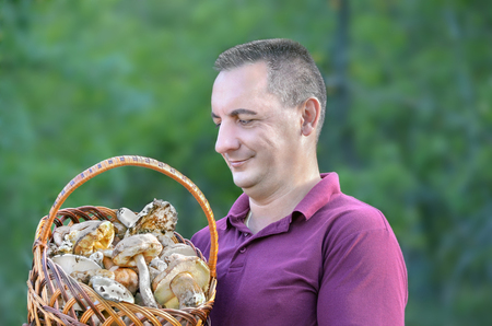 mushrooming: Mushrooming. A man with a basket of mushrooms in the forest Stock Photo