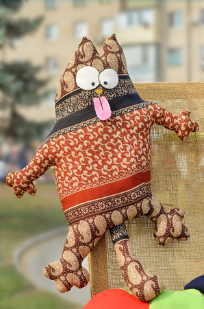 bulging: Cat with bulging eyes and protruding tongue. Rag toy souvenir. Funk, surprise, emotion