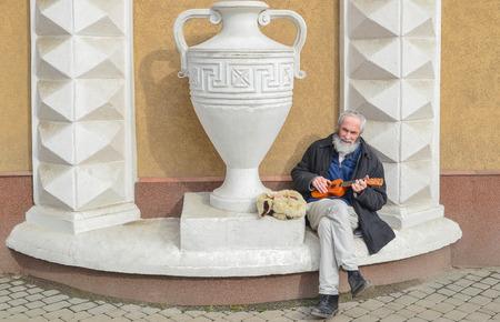 Street musician - guitarist. Elderly man earns money in the city of Ivano - Frankivsk, Ukraine Editorial
