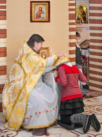 The rite of confession. The girl, a Christian confession in church of the priest on his knees.