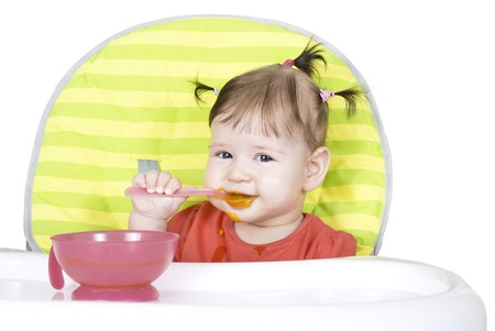 Little baby girl eating a vegetable puree in a highchair