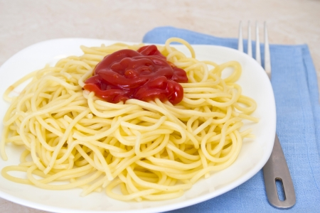 Spaghetti with ketchup in a bowl with a fork  photo
