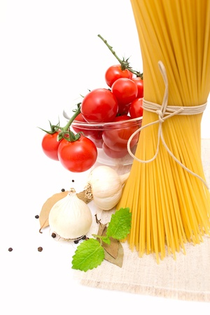 spaghetti, cherry tomatoes, onions, garlic, bay leaf, pepper on photo