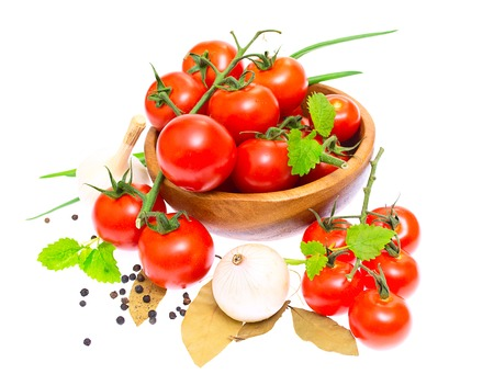 The branch of cherry tomatoes in a wooden bowl, onion, garlic, bay leaf, pepper isolated on white background photo