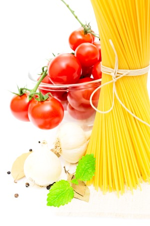 spaghetti, cherry tomatoes, onions, garlic, bay leaf, pepper on a white background photo