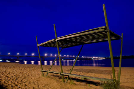 light traces: beach river bridge bench sunshade cement sand water lights reflection ripple light traces night twilight support wood recreation swimming shade