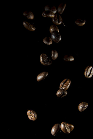 spot light: Flying, Falling grains of coffee Arabica on a black background, spot light studio
