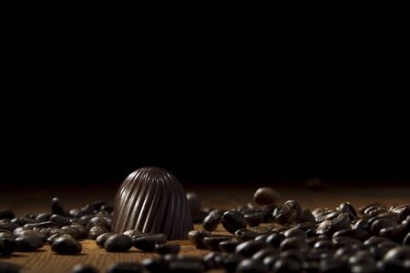 lighting background: Chocolate candy on a background of roasted coffee beans arabica, on wooden boards, dot studio lighting Stock Photo