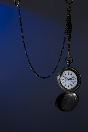 timekeeper: Antique silver pocket watch on a chain, spot colored studio light