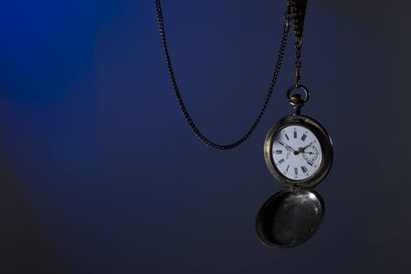 horologe: Antique silver pocket watch on a chain, spot colored studio light
