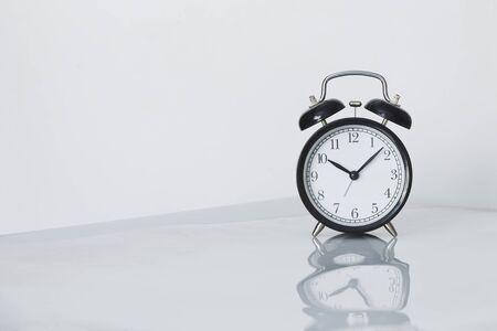 luz natural: Reloj de alarma retro en el fondo blanco, la luz natural, el minimalismo