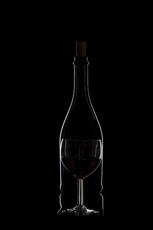 abstract liquor: Bottle of wine and glass with red wine on a black background, silhouette, studio lighting, minimalism
