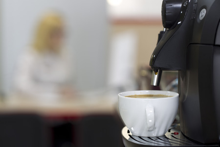 telecommuting: Coffee machine in the office interior, mixed light Stock Photo