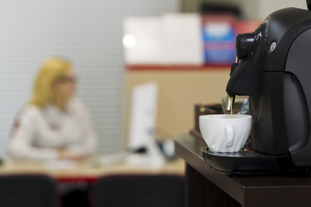 revision: Coffee machine in the office interior, mixed light Stock Photo