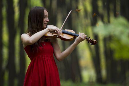 violinista: La chica en un vestido rojo que toca el violín en el bosque, luz suave Foto de archivo
