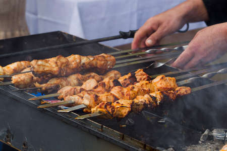the shish kebab: Shish kebab on skewers on the grill with hot coals, natural light Stock Photo