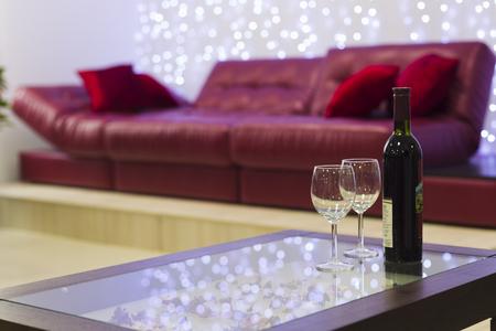 Bottiglia di vino con un bicchiere sul tavolino su uno sfondo di divano in pelle, luce artificiale