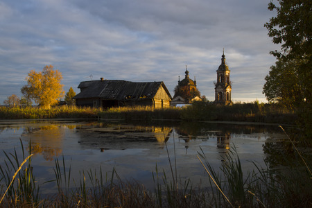 Autumn landscape with a pond, ruined wooden house and an old church, sunlight
