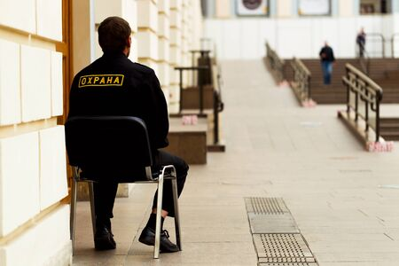 Security guard sitting on a chair at the door inside the room, natural light