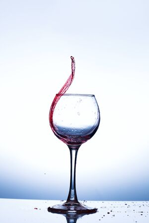 Wine splashing in glass, acrylic background, studio lighting