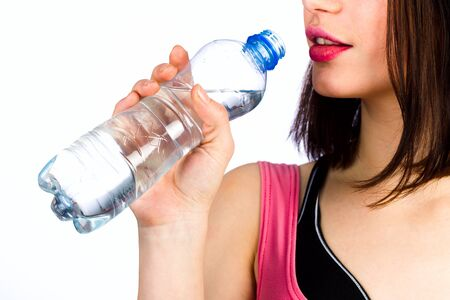 Young girl with a bottle of drinking water on a white background, studio lighting
