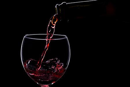 ワイングラスや黒の背景、シルエット、ミニマリズム、スタジオ照明のワインのボトルの赤ワイン 写真素材