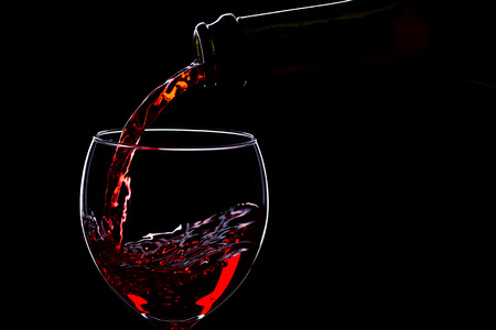 Red wine in wine glasses and wine bottle on a black background, silhouette, minimalism, studio lighting Stock Photo