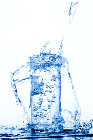 Water pours into the glass, monochromatic background, studio light Stock Photo