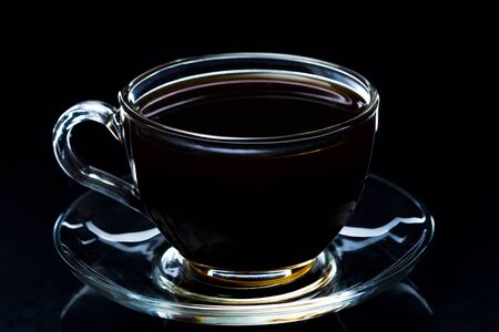 Hete zwarte koffie rookt in een glazen beker op een zwarte achtergrond, studio licht