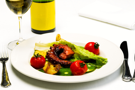 Seafood dish with fried octopus tentacles and vegetables with a bottle and a glass of wine on a white tablecloth background, studio light