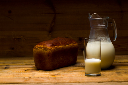 Milk from a glass jug poured into a glass, a loaf of rye bread, ears of corn on the background of wooden boards, studio light Stock Photo