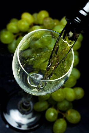 White wine pours from a bottle into a glass, a bunch of grapes, a black background, studio light Stock Photo