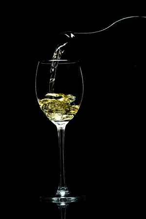white wine: Wine is pouring from a bottle into a glass on a black background, studio light Stock Photo