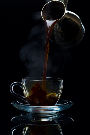 Hot black coffee is poured from the Turks into a clean glass cup, black background, studio light