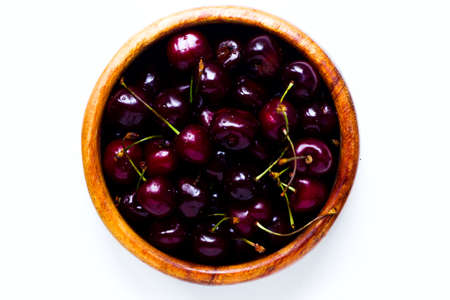 Cherry in a wooden plate on a white background, natural light