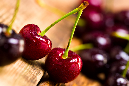 Cherry in a wooden bowl on the background of wooden boards, studio light