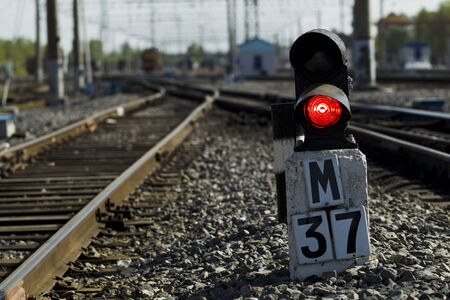 Railway semaphore burning red light on a background of a rail locomotive and sunny day Stock Photo