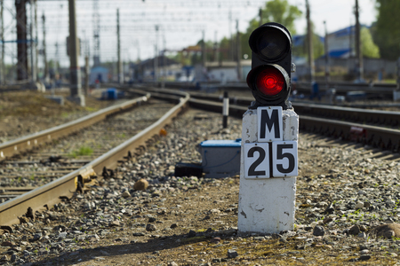 freight train: Railway semaphore burning red light on a background of a rail locomotive and sunny day Stock Photo